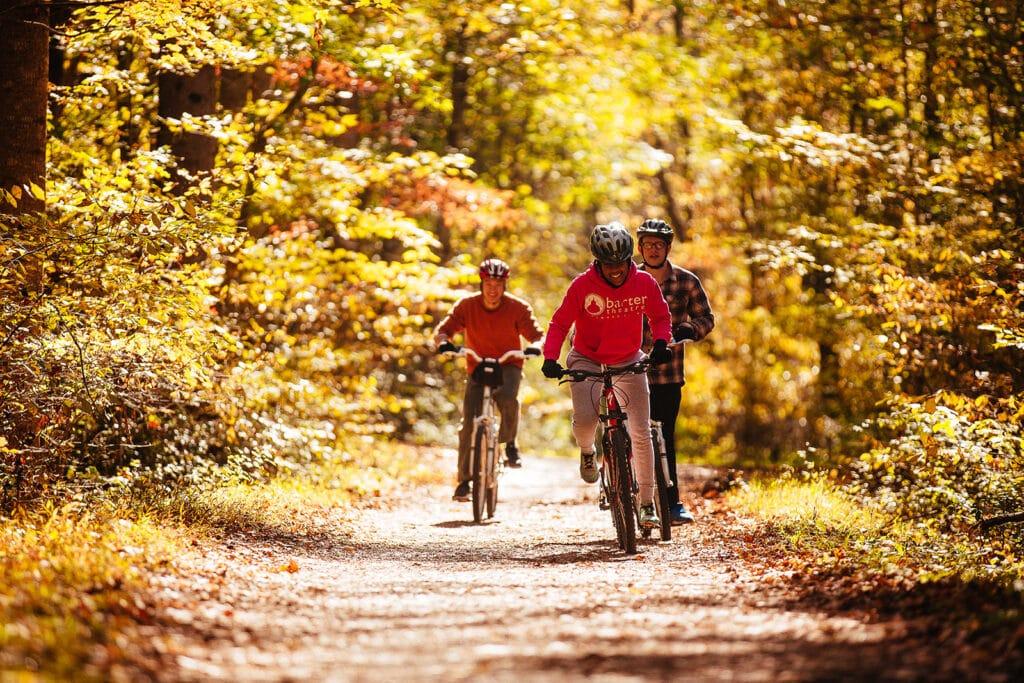 Three men riding bikes through fall scenery
